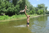 Father and son swimming in the river. — Stockfoto