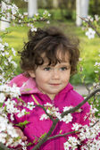 Spring in the garden a little girl holding a cherry branch. — Stockfoto