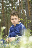 Sad boy in the woods. — Stock Photo