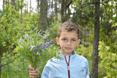 Boy standing in the woods with a bouquet of flowers. — Stockfoto