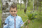 Boy standing in the woods with a bouquet of flowers. — Stock Photo