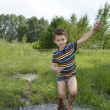 Barefoot boy runs through a puddle. — Stock Photo #47213471
