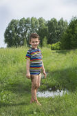 Dirty rural barefoot boy standing near a puddle. — Stock Photo