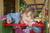 En liten flicka som leker på lekplatsen och skrattar. — Stockfoto