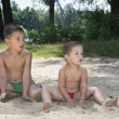 Summer at the beach sitting on the sand two children and watch c — Stock Photo #50100595