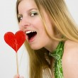 Young woman eating heart of candy — Stock Photo