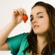 Beautiful young woman showing strawberry — Stock Photo