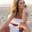 Stock Photo: Beautiful woman in white dress at the beach