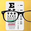 Stock Vector: Eyeglasses over snellen eye chart