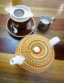 Teapot with tea cozy, tea cup and a jug of milk — Stock Photo