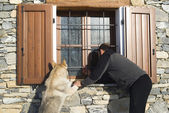 Man and dog looking at window — Stock Photo