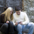 Stock Photo: Young couple using mobile phone