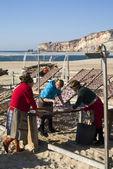 Portugisiska kvinnor torkning fisk på stranden i nazare — Stockfoto