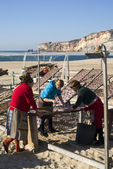 Portuguese women drying fish on the beach in Nazare — Stock Photo