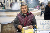 Poor elderly woman sells chestnuts — Stock Photo