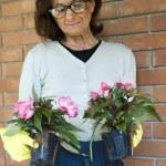 Smiling senior woman holding flowers — Stock Photo #18804025