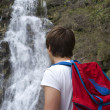 Hiker standing near waterfall — Stock Photo #18805713