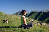 Woman sitting on grass in mountains relaxing — Stock Photo