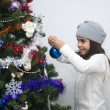 Girl putting ornament on Christmas tree - Stock Photo