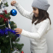 Stock Photo: Girl putting ornament on Christmas tree