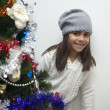 Girl behind Christmas tree - Stock Photo