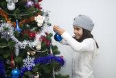 Garota colocando ornamento na árvore de natal — Fotografia Stock