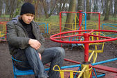 Sad boy at a old abandoned playground — Stock Photo