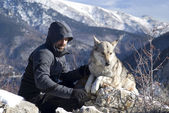 Man with dog hike in winter mountains — Stock Photo