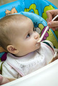 Baby girl being spoon fed — Stock Photo