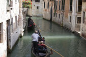 Gondoliers rowing gondola in canal — Stock Photo