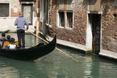Gondolier rowing gondola in canal — Stock Photo