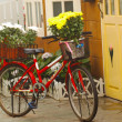 This vintage red girls bicycle has beautiful yellow flowers in a basket on the front of the bike — Stock Photo #30230547