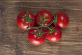 Tomatoes on wooden background — Stock Photo
