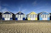 Row of brightly coloured beach huts — Stock Photo