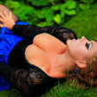 Beautiful young plus size woman lying on green grass with full c — Stok fotoğraf