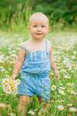 Girl in a field of daisies with a bouquet — Stock Photo