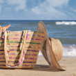 Women's hat and bag on the beach - Stok fotoğraf