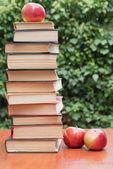Livres et pommes sur la table — Photo