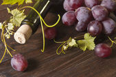 Macro shot of grapes and bottle of wine on wooden board. Background — Stock Photo