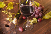 A bottle of wine with glass on a barrel as background — Stock Photo