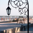Silhouette wrought park lantern against the beach and sea in sum — Stok fotoğraf