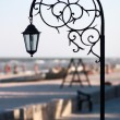 Silhouette wrought park lantern against the beach and sea in sum — Zdjęcie stockowe