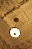 Bronze chandelier view from below with moldings — Stock Photo