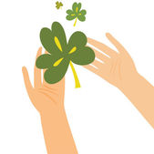 Hands holding clover leaf — Stock Vector
