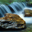 Stock Photo: Small waterfall and pair of river rocks