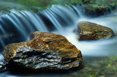 Small waterfall and a pair of river rocks — Stock Photo