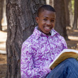 African teenager boy reading a book outdoors — Stock Photo #19241727