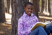 African teenager boy reading a book outdoors — Stock Photo
