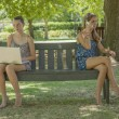 Two girls with laptop and smart phone outdoor — Stock Photo