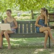 Stock Photo: Two girls with laptop and smart phone outdoor
